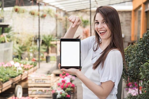 Glückliche frau, die auf digitale tablette mit leerem weißem bildschirm zeigt