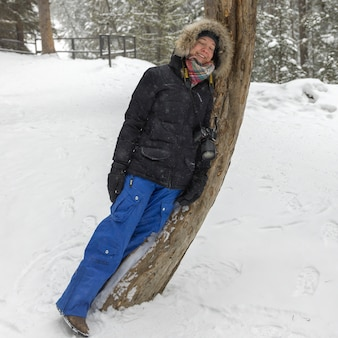 Glückliche frau, die auf einem baum im schnee sich lehnt, bedeckte wald, johnston-schlucht, banff-nationalpark, alberta,
