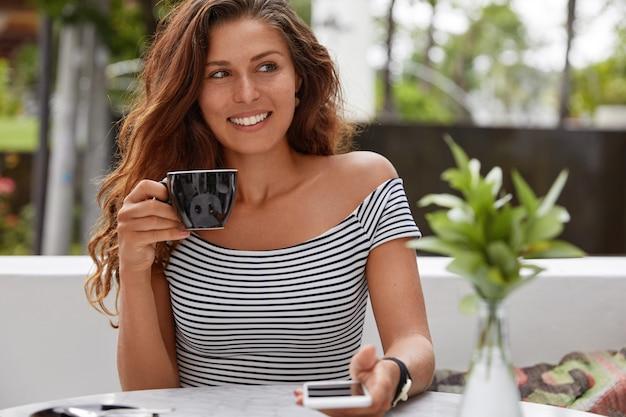 Glückliche frau, die auf einem kaffeehaus sitzt