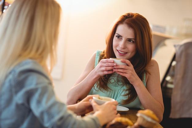 Glückliche frau, die auf freund an der kaffeestube hört