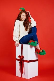 Glückliche frau, die auf großem weihnachtsgeschenk sitzt