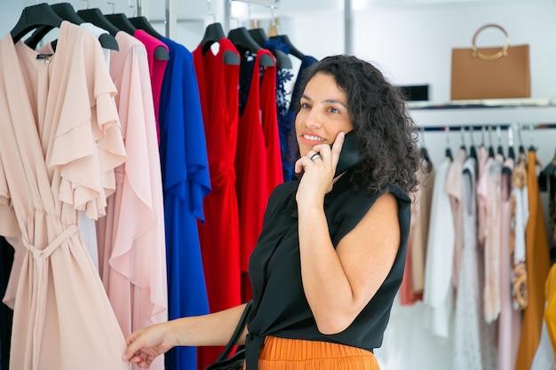 Glückliche frau, die auf handy spricht, während sie kleidung wählt und kleider auf gestell im modegeschäft durchsucht. mittlerer schuss. boutique-kunden- oder einzelhandelskonzept
