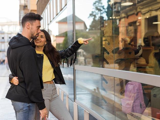 Glückliche frau, die auf jungem mann auf shopfenster umarmt und darstellt