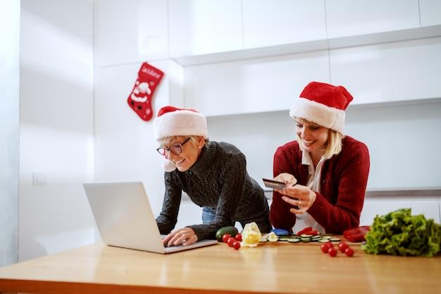 Glückliche frau, die auf küchentheke stützt und kreditkarte betrachtet. mutter tippt auf laptop. beide haben weihnachtsmützen auf den köpfen. zeit für weihnachtseinkäufe.