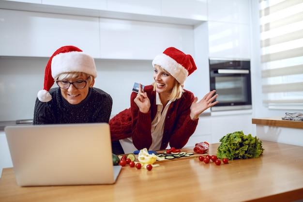 Glückliche frau, die auf küchentheke stützt und kreditkarte hält. mutter tippt auf laptop. beide haben weihnachtsmützen auf den köpfen. zeit für weihnachtseinkäufe.