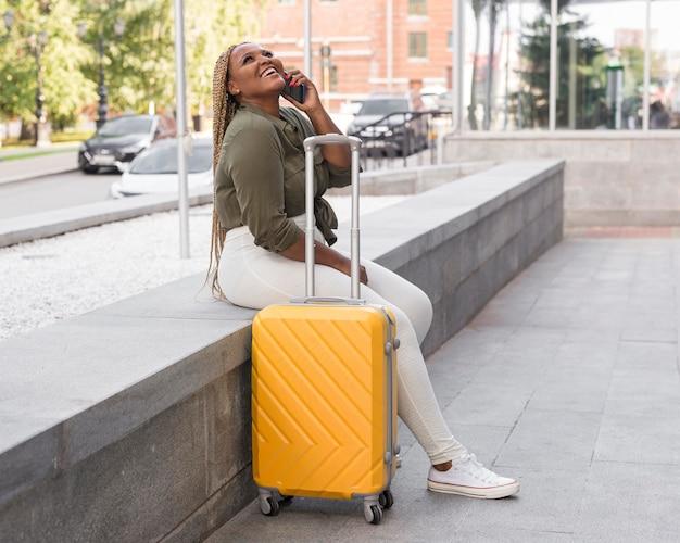 Glückliche frau, die auf reisen sitzt und am telefon spricht