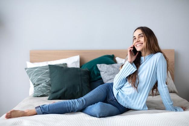 Glückliche frau, die auf smartphone zu hause auf der couch spricht. menschen-, technologie- und kommunikationskonzept.