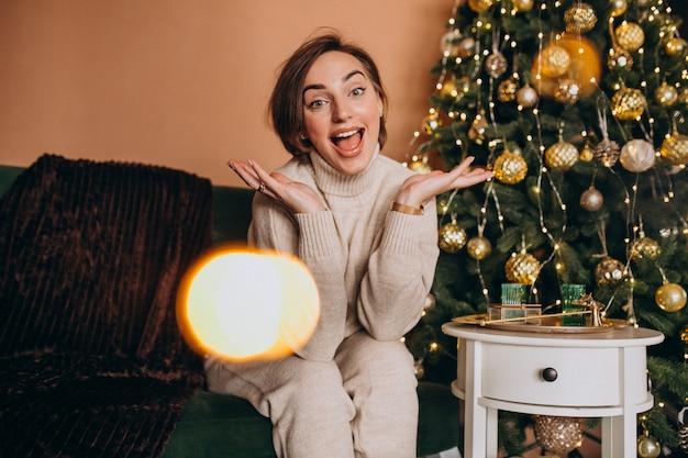 Glückliche frau, die auf sofa durch den weihnachtsbaum sitzt
