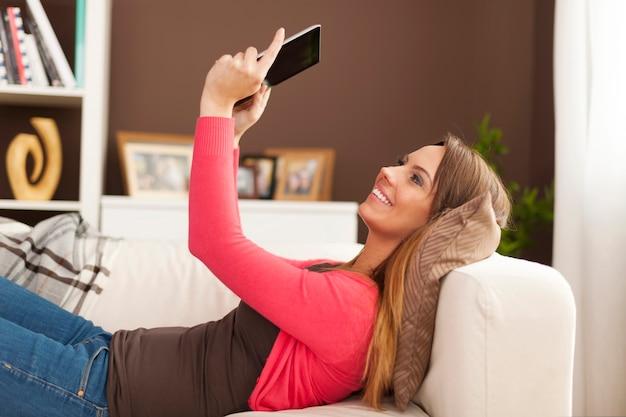Glückliche frau, die auf sofa liegend und digitales tablett benutzt