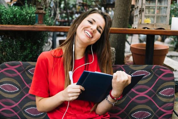 Glückliche frau, die auf sofa mit dem tagebuch hört musik auf kopfhörer sitzt