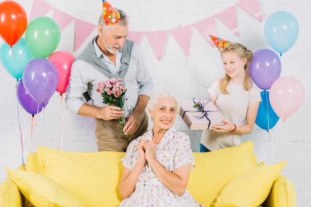 Glückliche frau, die auf sofa vor dem ehemann und enkelin hält geburtstagsgeschenke sitzt