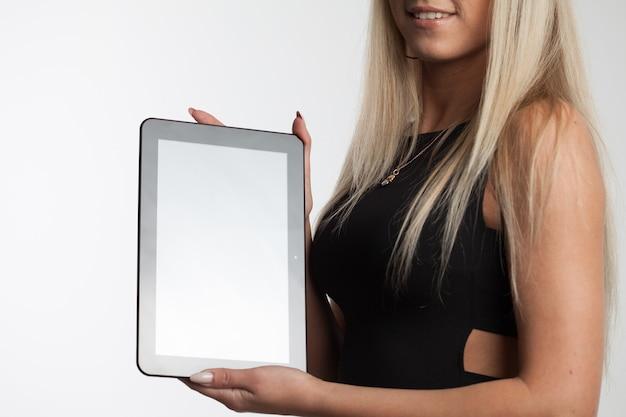 Glückliche frau, die auf tablet-computer zeigt