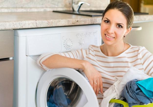 Glückliche frau, die auf waschmaschine sich lehnt