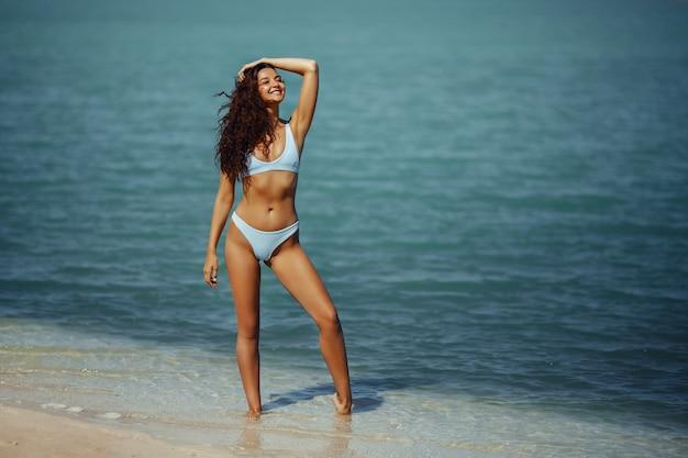 Glückliche frau, die aufgeregt in einem blauen bikini am strand steht, gebräunt, schlankes mädchen im badeanzug, das genießt