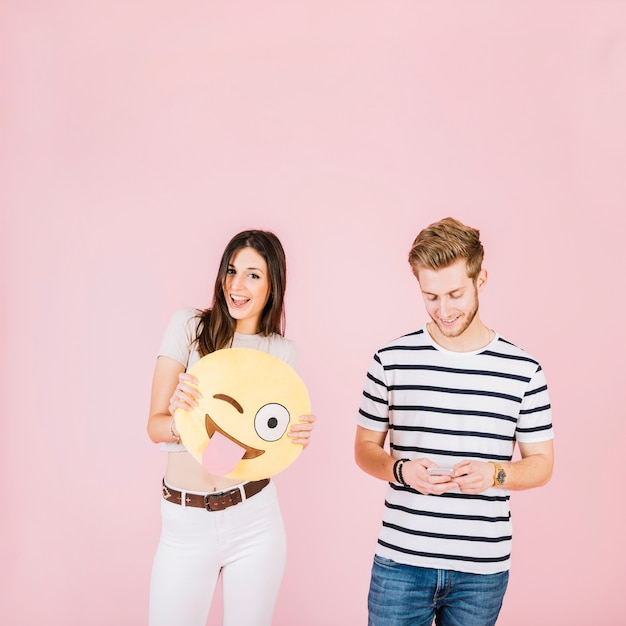 Glückliche frau, die augenenji emoji nahe ihrem freund mit mobiltelefon blinzelnd hält