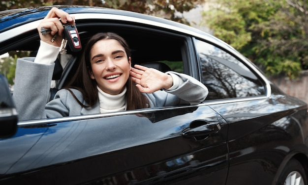 Glückliche frau, die aus dem fenster schaut und neue autoschlüssel zeigt, kaufte neues auto