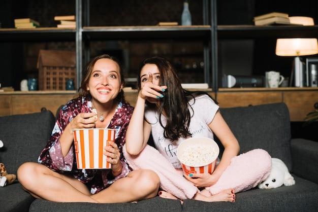 Glückliche frau, die außer ihrem freund zeigt finger beim überwachen des films sitzt