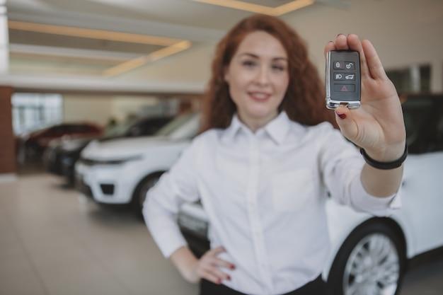 Glückliche frau, die autoschlüssel zu ihrem neuen automobil hält