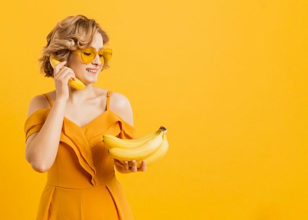 Glückliche frau, die banane als telefon benutzt