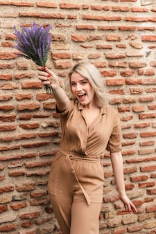 Glückliche frau, die beim halten des straußes der lavendelblumen aufwirft