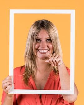 Glückliche frau, die bilderrahmen vor ihrem gesicht hält und zeigefinger in richtung zur kamera zeigt