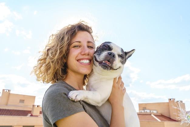 Glückliche frau, die bulldogge hält. horizontale ansicht der frau mit haustier im freien. lebensstil mit tieren.