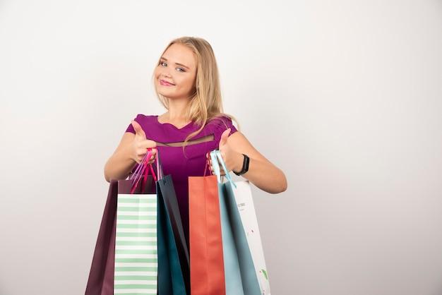 Glückliche frau, die bunte einkaufstaschen trägt und daumen hoch macht.