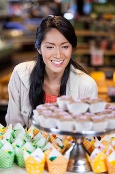 Glückliche frau, die cupcakes betrachtet