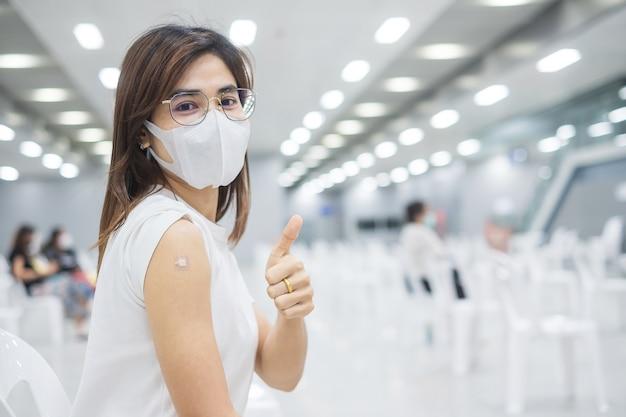 Glückliche frau, die daumen zeigt, nachdem sie den impfstoff erhalten hat. impfung, impfung, impfung und coronavirus (covid-19) pandemie