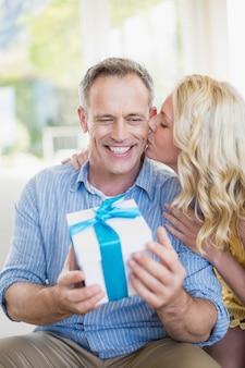 Glückliche frau, die dem ehemann im wohnzimmer geschenk gibt
