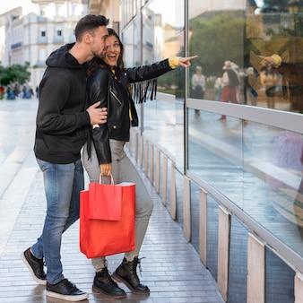 Glückliche frau, die dem jungen mann auf shopfenster darstellt