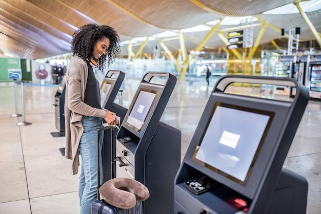 Glückliche frau, die den abfertigungsautomaten am flughafen erhält die bordkarte verwendet.