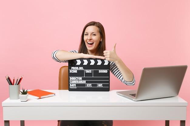 Glückliche frau, die den daumen zeigt und sich auf den klassischen schwarzen film stützt, der eine klappe macht, während sie mit laptop im büro sitzt