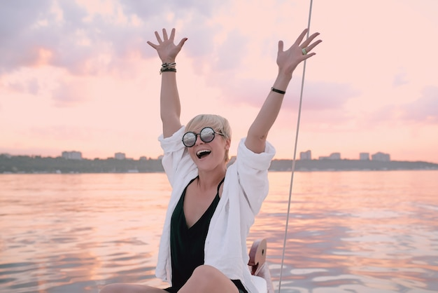 Glückliche frau, die den sonnenuntergang auf der yacht im meer genießt