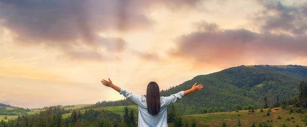 Glückliche frau, die den sonnenuntergang genießt, während sie auf dem berg steht