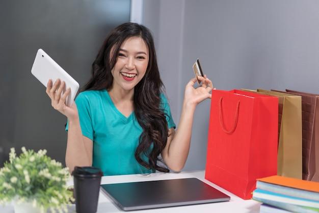 Glückliche frau, die digitale tablette für das on-line-einkaufen mit kreditkarte verwendet