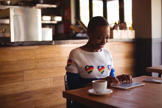 Glückliche frau, die digitales tablett beim kaffee verwendet