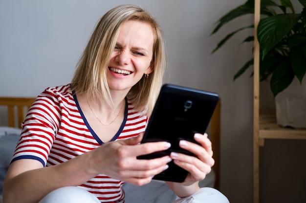 Glückliche frau, die digitales tablett für videoanruffreunde und -eltern verwendet, lächelndes mädchen, das zu hause auf bett spaßgruß online durch computer-webcam sitzt, die videoanruf macht
