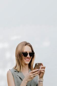 Glückliche frau, die draußen an ihrem telefon spielt