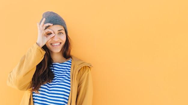 Glückliche frau, die durch tragende strickmütze des handbinokularen schaut