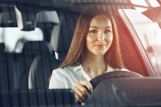 Glückliche frau, die ein auto fährt und lächelt