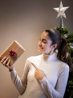 Glückliche frau, die ein geschenk anhält