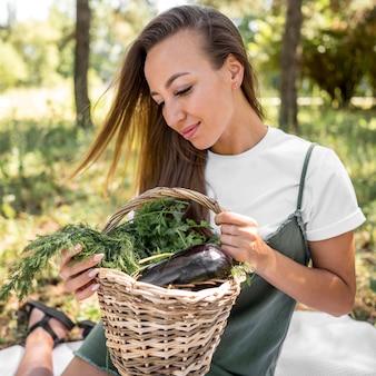 Glückliche frau, die ein picknick mit gesunden snacks hat