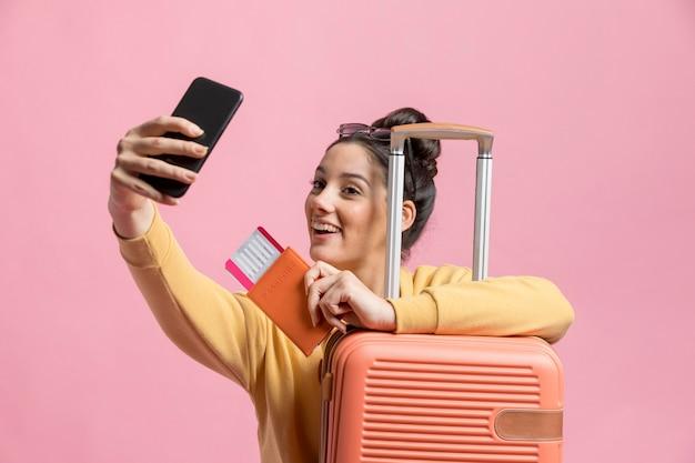 Glückliche frau, die ein selfie mit ihrem pass und gepäck nimmt