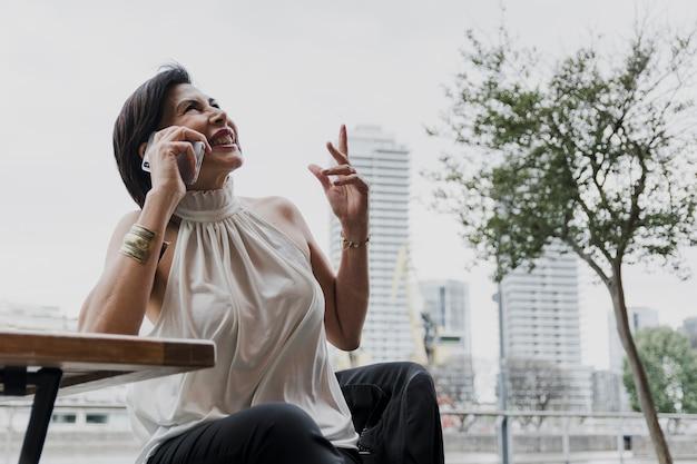 Glückliche frau, die ein telefon auf stadthintergrund hält