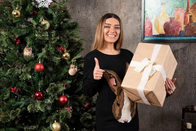 Glückliche frau, die ein weihnachtsgeschenk hält und einen daumen nach oben zeigt. hochwertiges foto