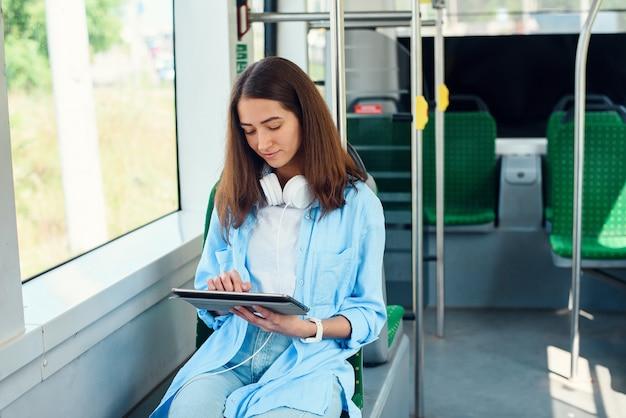 Glückliche frau, die eine tafel oder ein e-book in einem bahnhof liest, während sie auf öffentliche verkehrsmittel wartet