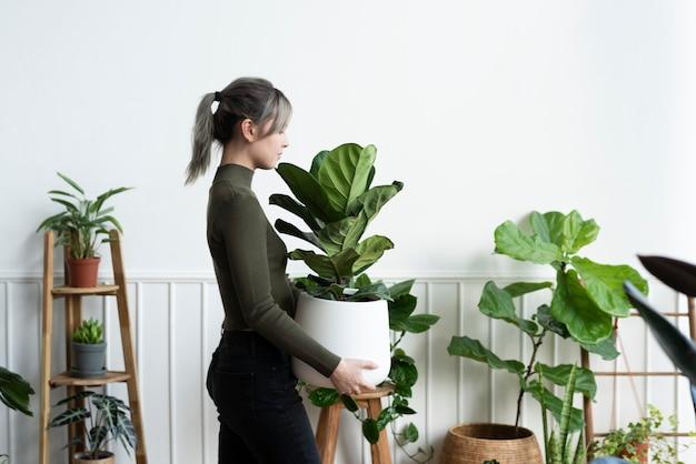 Glückliche frau, die eine zimmerpflanze trägt