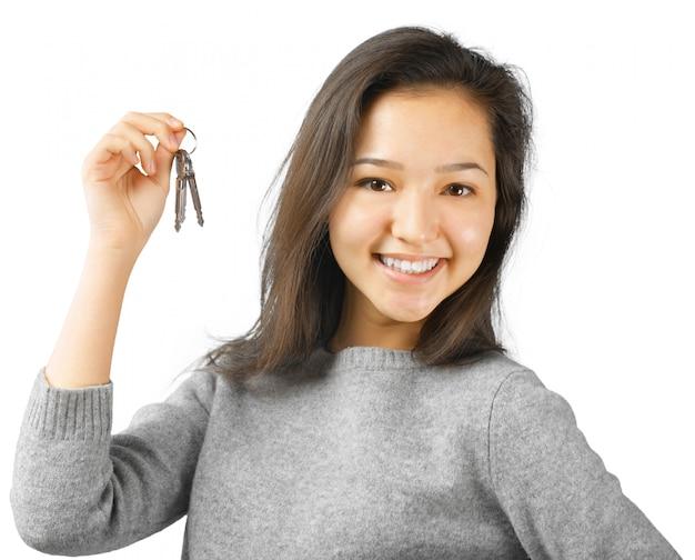 Glückliche frau, die einen autoschlüssel hält