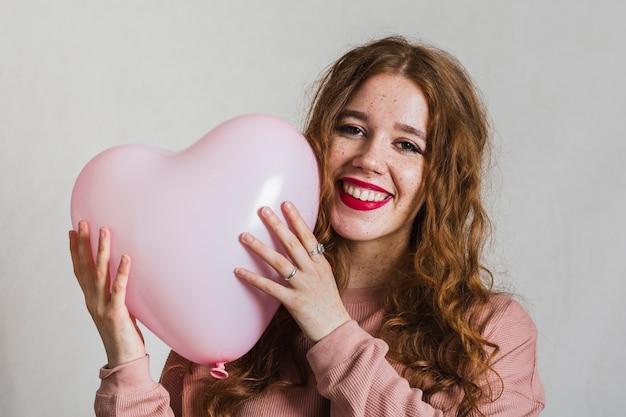 Glückliche frau, die einen ballon umarmt